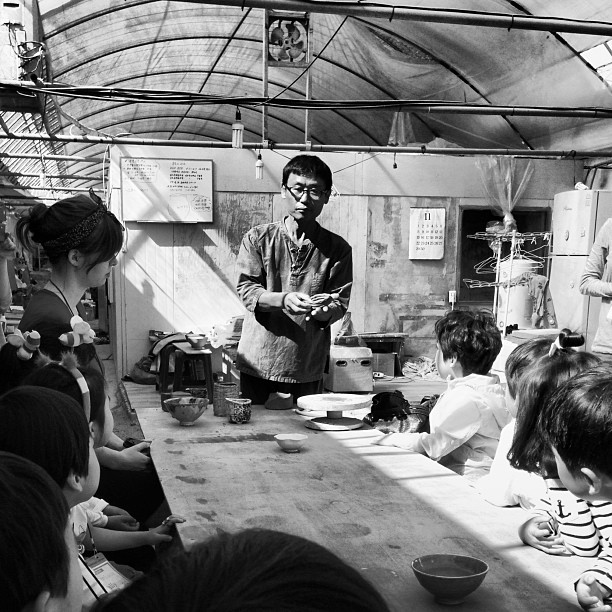 Teachers and students all learning the craft of clay pottery.